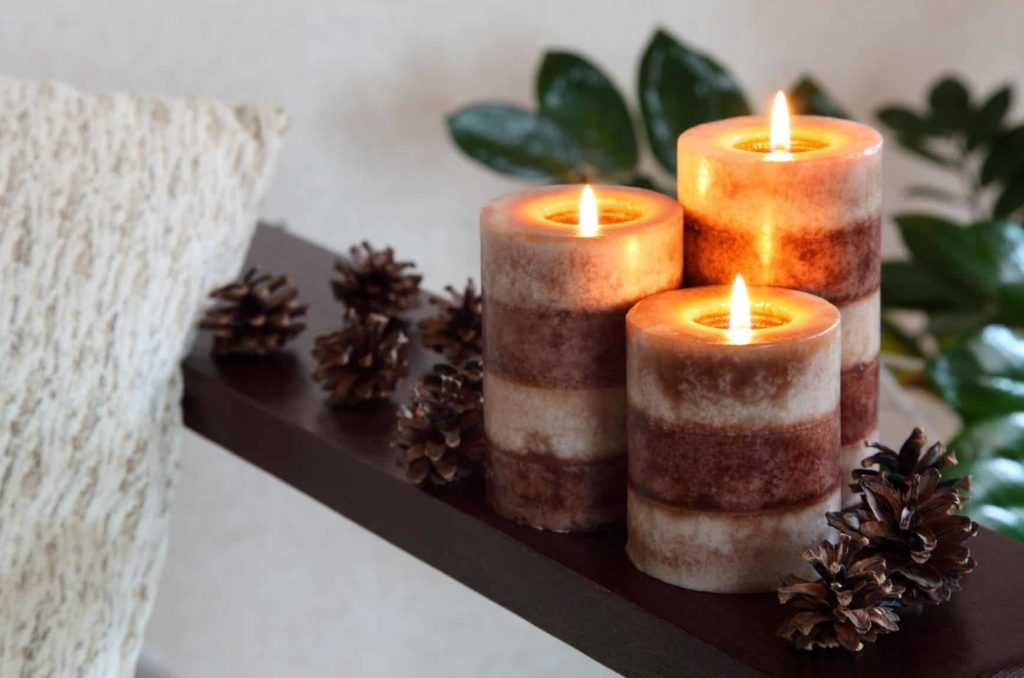 Three candles burning on a countertop besides some pinecones and a warm blanket.