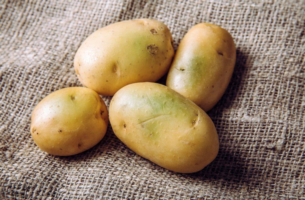 Four green potatoes on a potato sack.