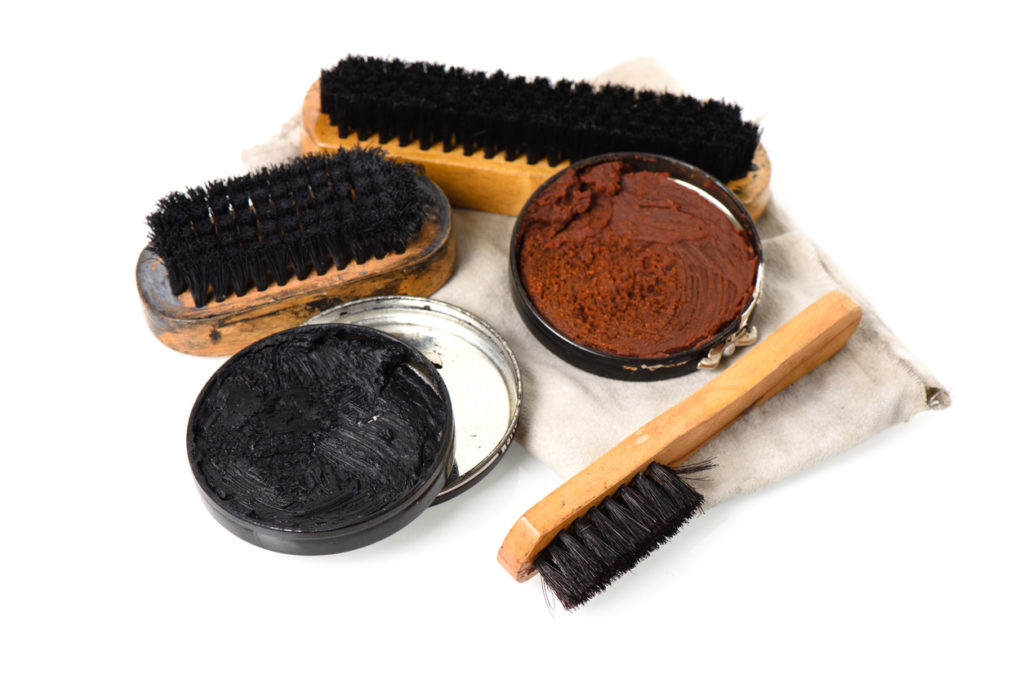 A tin of both black and brown shoe polish sits on a shining cloth besides polishing brushes.