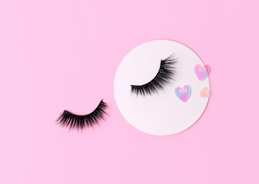 a pair of false eyelashes on a pink background with heart-shaped glitter beside them